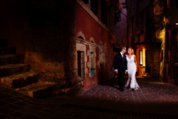 Bride and groom walk down alleyway at night
