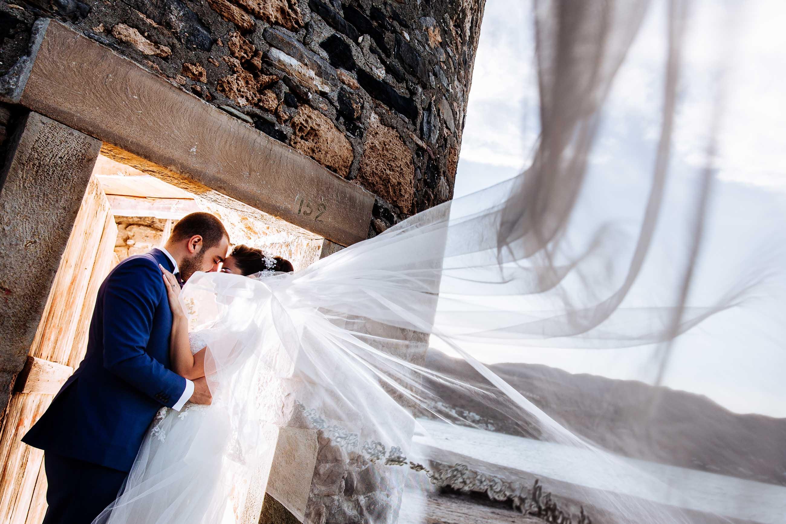 Bride and groom, veil blowing in the wind