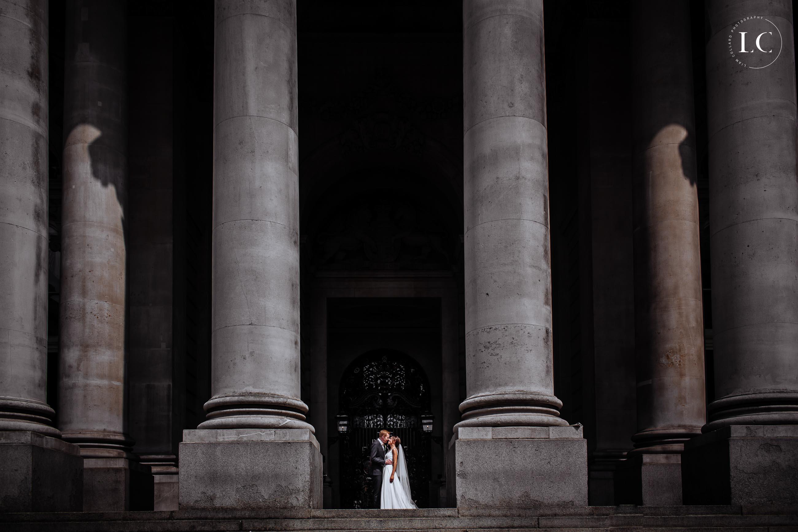 Bride and groom between two pillars