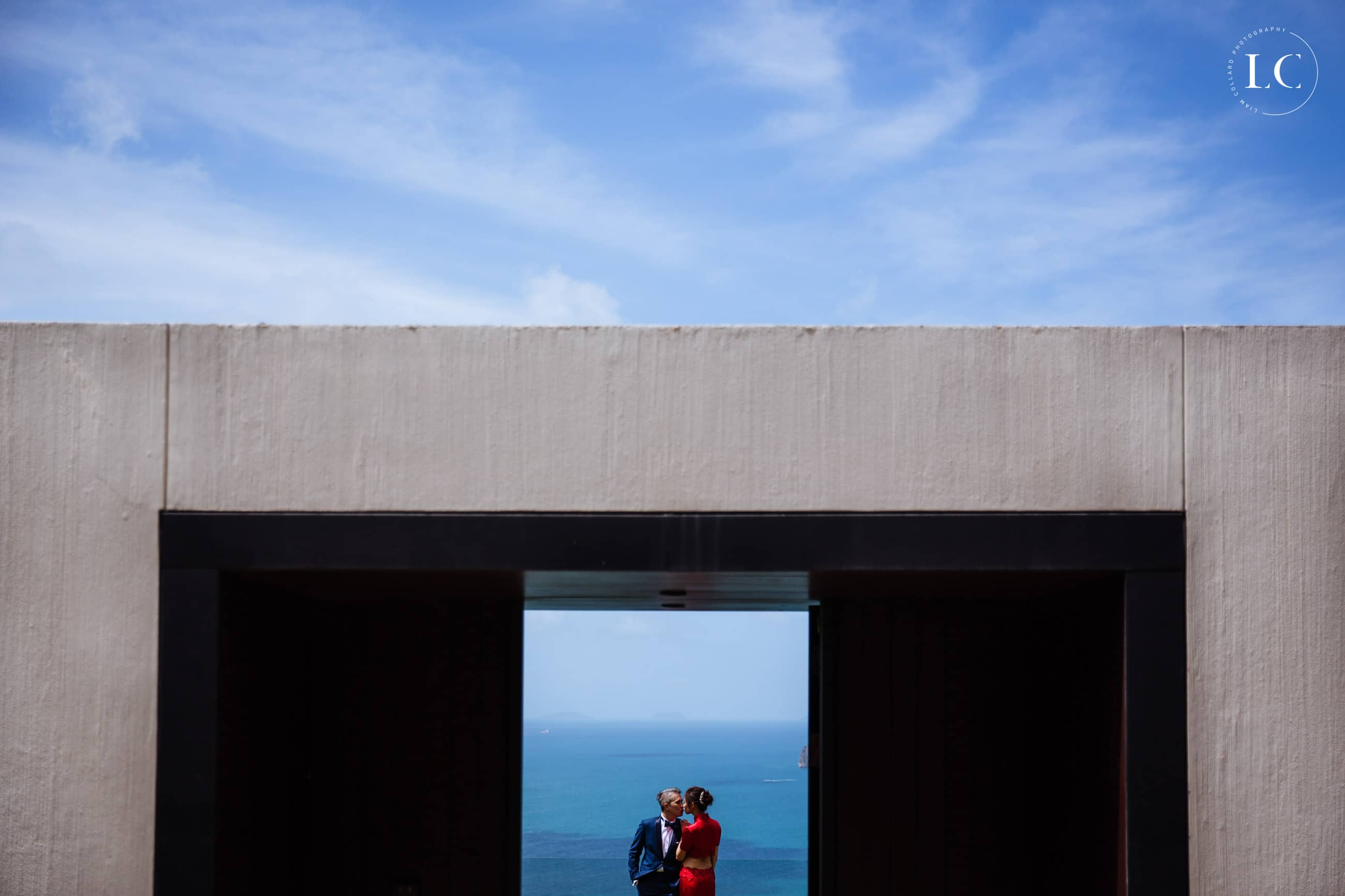 Couple embracing beside ocean and house