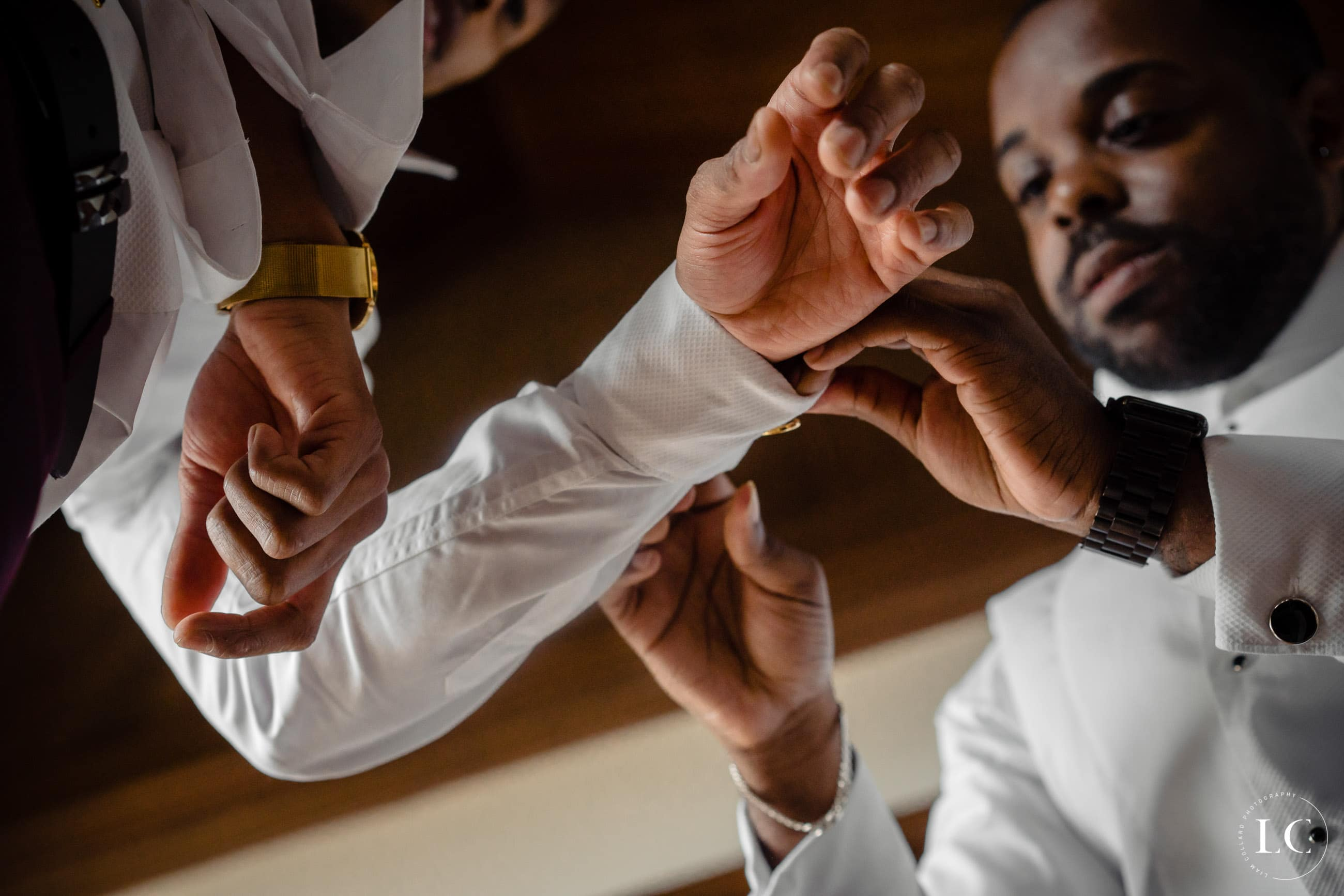 Groomsmen help groom do his cufflinks