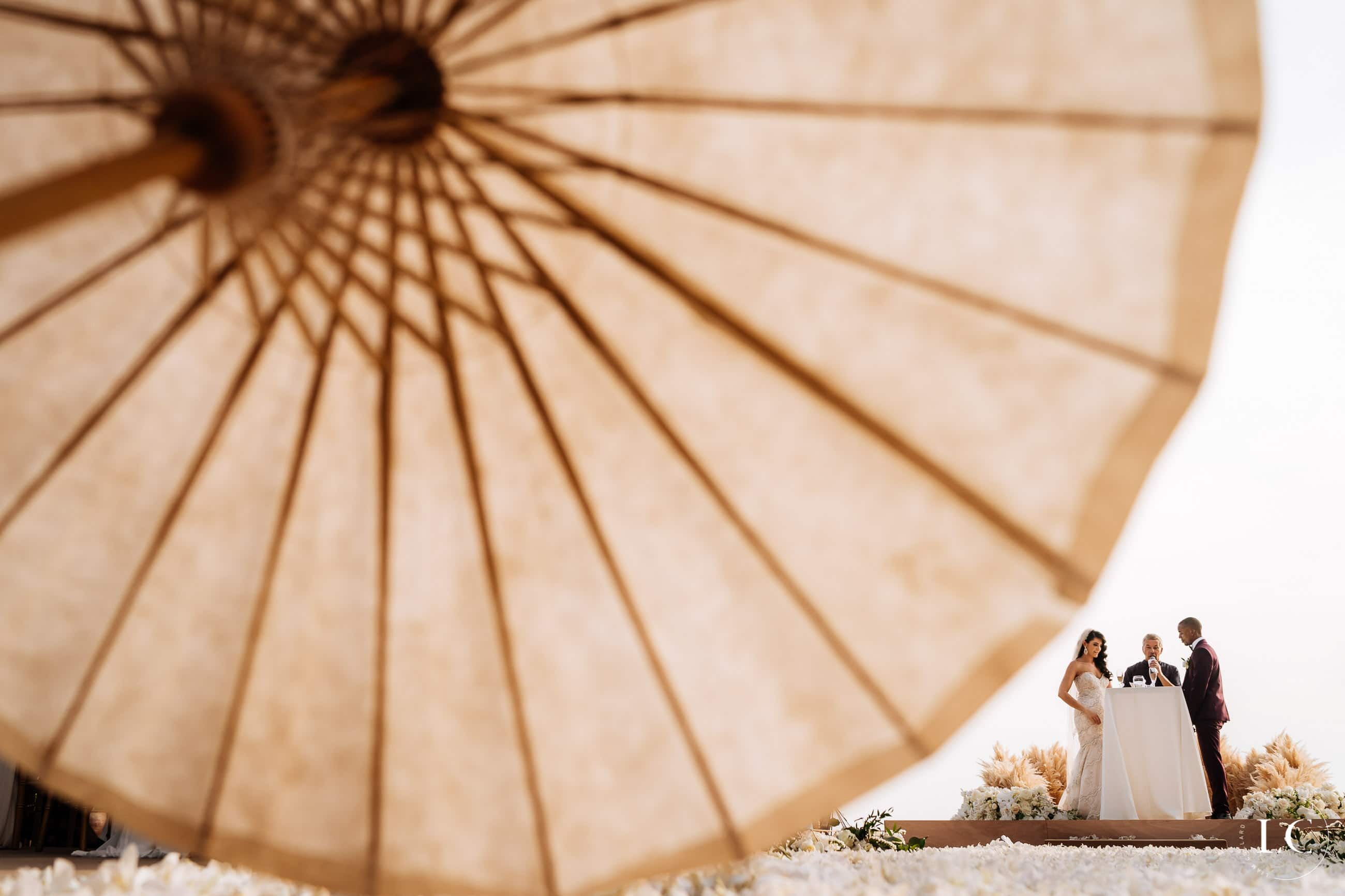 Far angle shot with umbrella in the forefront of bride and groom