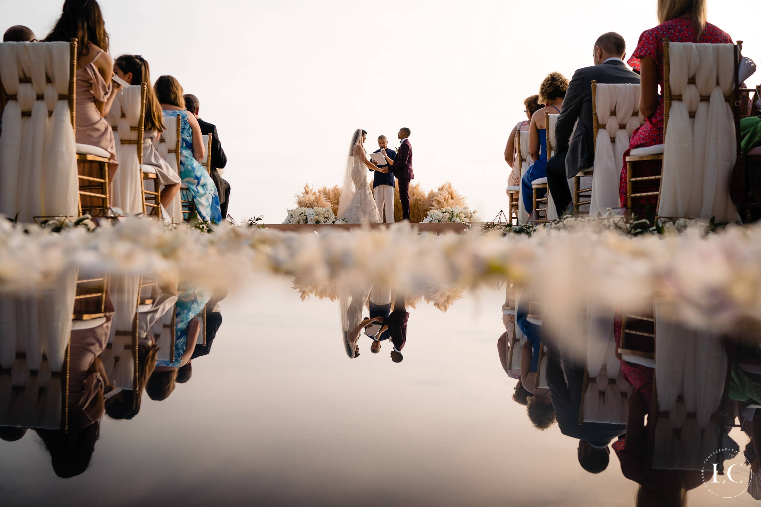 Wide shot with water reflection of bride and groom at altar