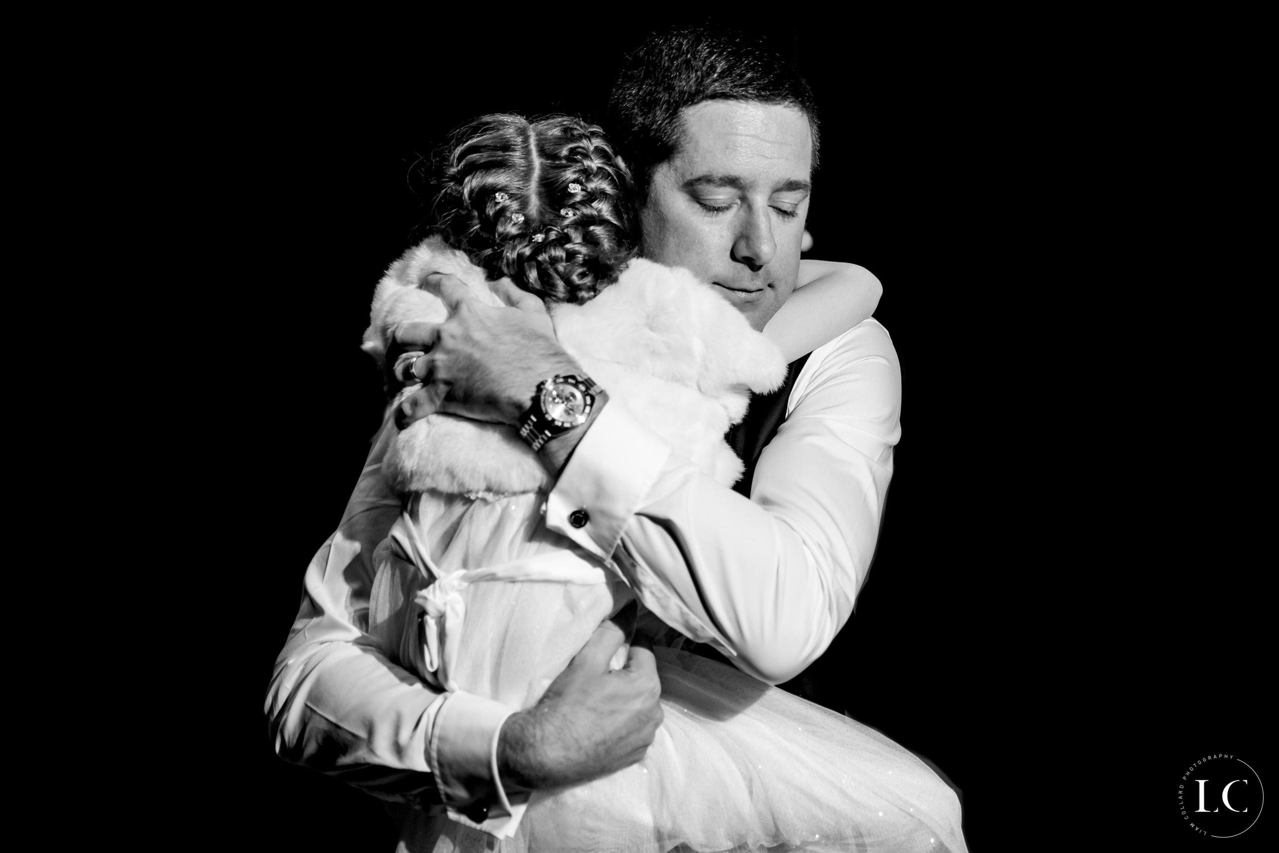 Groom hugging child