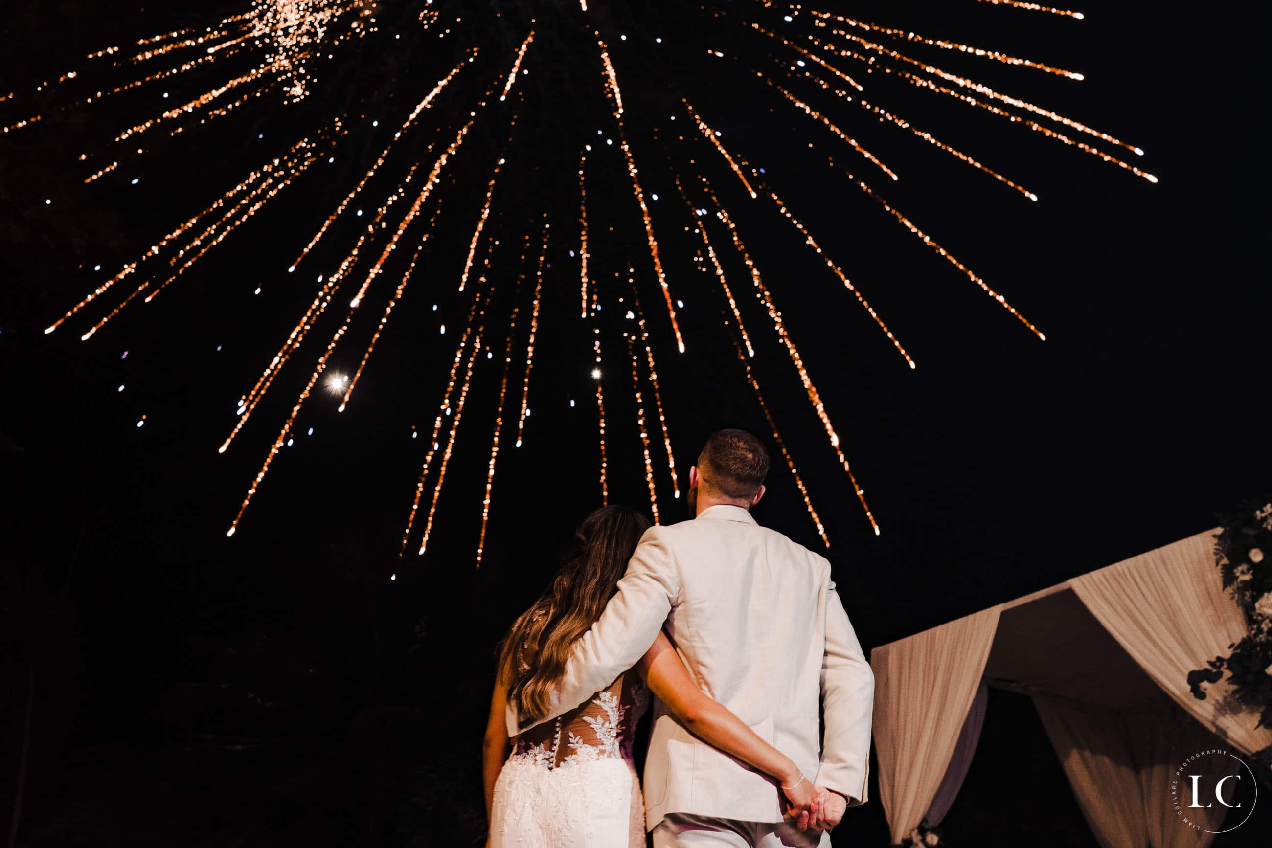 Bride and groom looking at fireworks
