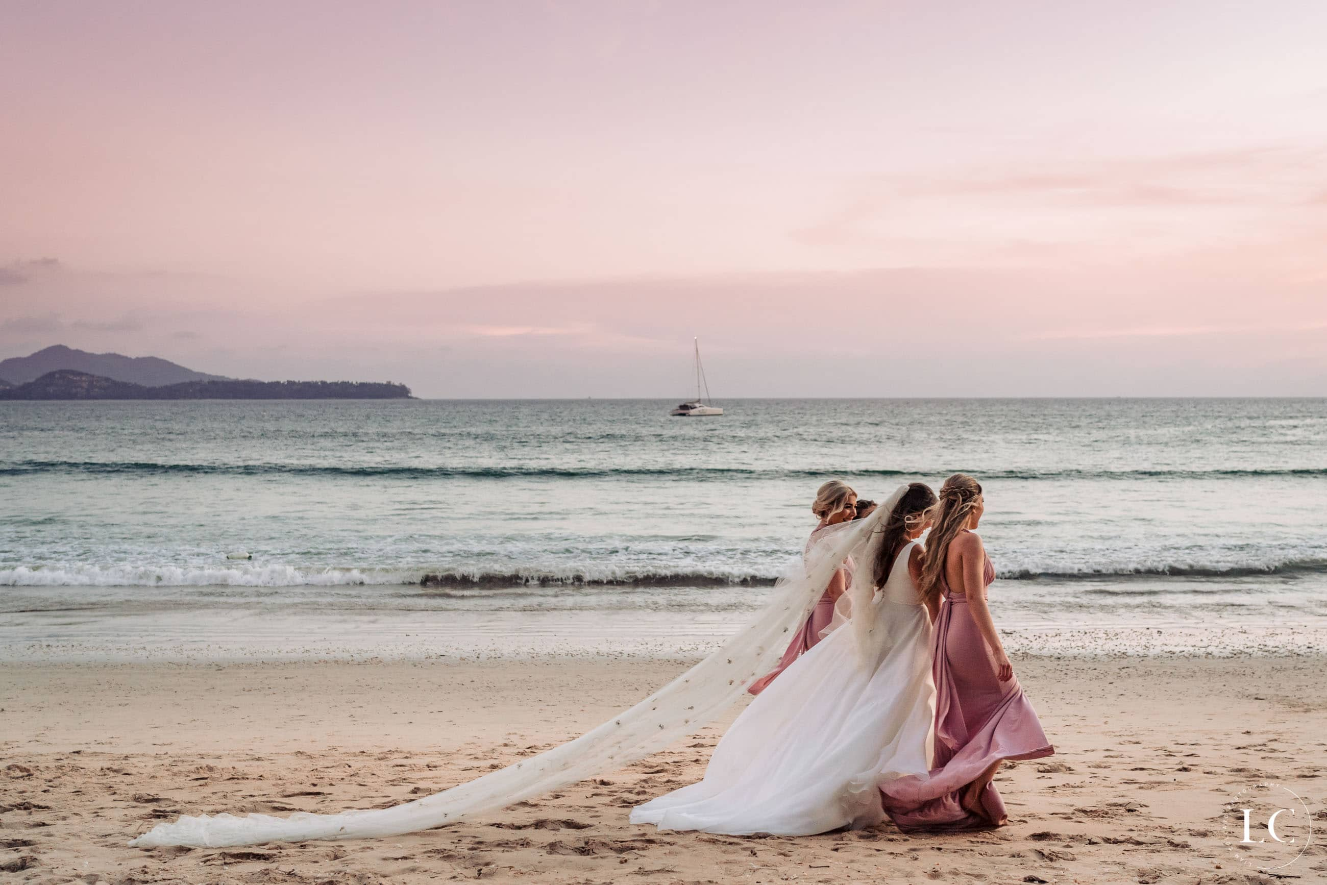 Bride walking on beach with bridesmaids