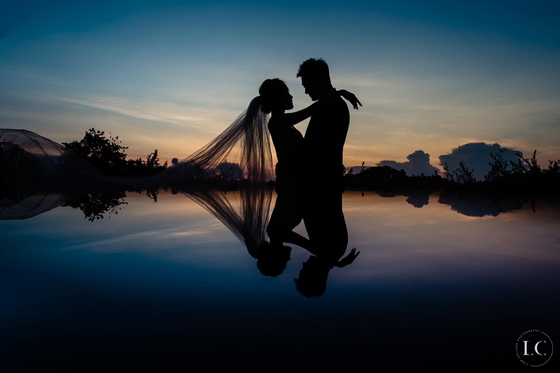 Bride and groom at sunset in water