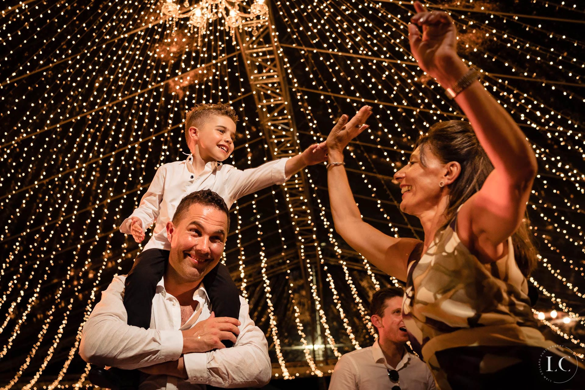 Child on man's shoulders at wedding