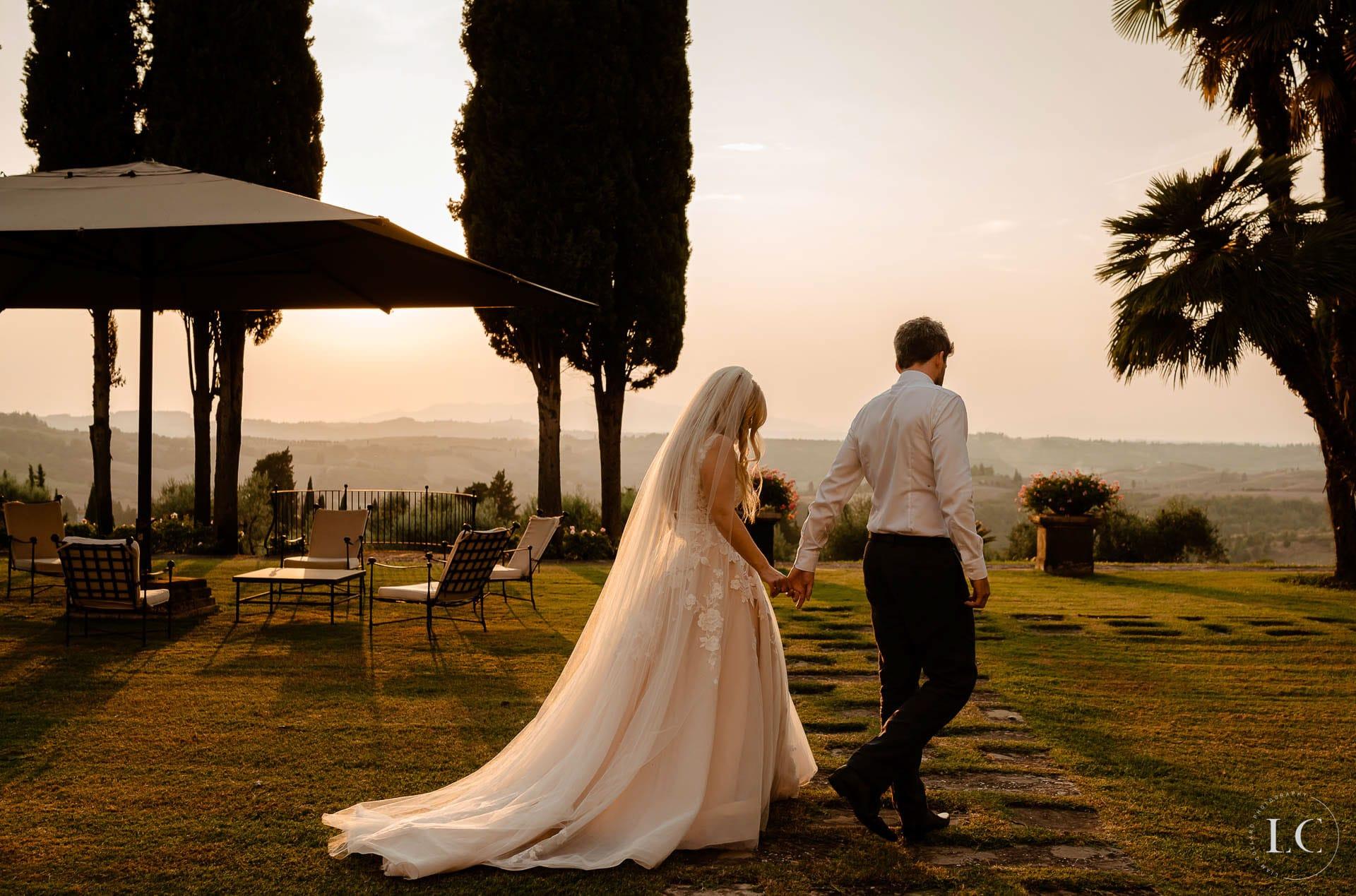 Newly weds walking outside at sunset