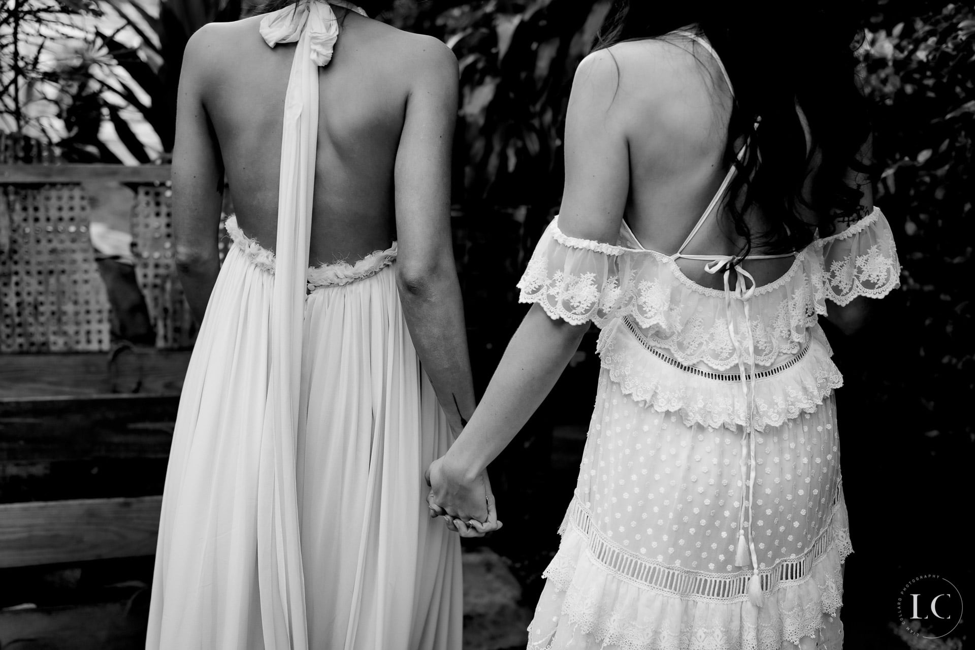Same sex brides holding hands