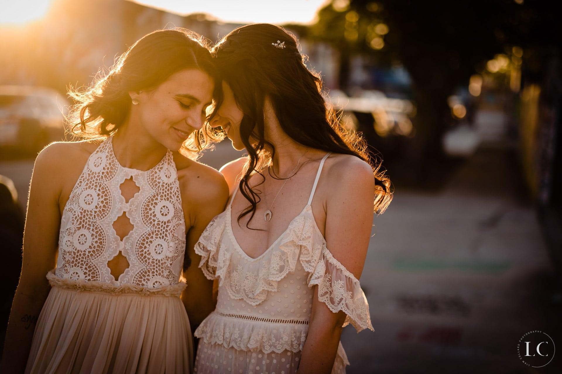Same sex brides embracing sunset